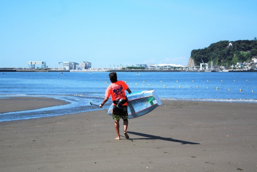 Photo of Mr. Yoneken holding a SUP board